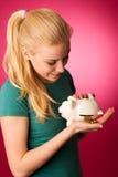 La donna con il porcellino salvadanaio in mani ha eccitato alla cassaforte per conservare il risparmio Fotografia Stock