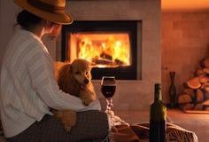 La donna con il suo cane si siede al pavimento ed al vino bevente immagine stock libera da diritti