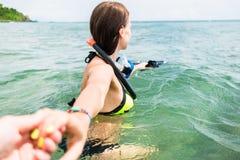 La donna con immersione subacquea googla il partner di trascinamento al mare Fotografia Stock
