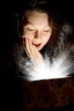 La donna con indicatore luminoso astratto da un contenitore di regalo Fotografie Stock
