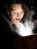 La donna con indicatore luminoso astratto da un contenitore di regalo Fotografie Stock Libere da Diritti