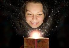 La donna con indicatore luminoso astratto da un contenitore di regalo Fotografia Stock