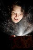 La donna con indicatore luminoso astratto da un contenitore di regalo Immagini Stock