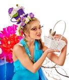 La donna con l'acconciatura dei fiori nel canestro di pasqua tiene il coniglietto Fotografia Stock