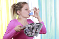 La donna con l'allergia della polvere della casa e l'asma spruzzano Fotografie Stock