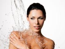 La donna con l'ente bagnato e spruzza dell'acqua Fotografia Stock