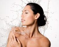 La donna con l'ente bagnato e spruzza dell'acqua Immagine Stock