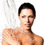 La donna con l'ente bagnato e spruzza dell'acqua Immagini Stock Libere da Diritti