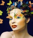 La donna con l'estate creativa compone come il fondo colorato luminoso del primo piano leggiadramente della farfalla fotografia stock