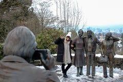 La donna con l'inverno copre, posando per una foto con le statue fotografia stock
