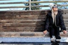 La donna con l'inverno copre, sedendosi su un banco di legno con neve fotografia stock