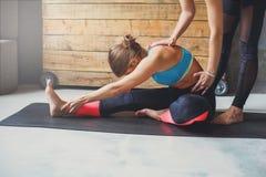 La donna con l'istruttore di yoga nella classe, si siede la posa di andata della curvatura Fotografia Stock