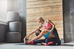 La donna con l'istruttore di yoga nella classe, si siede la posa di andata della curvatura Immagini Stock Libere da Diritti