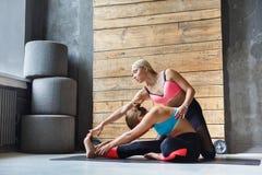 La donna con l'istruttore di yoga nella classe, si siede la posa di andata della curvatura Fotografie Stock Libere da Diritti