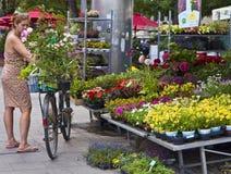 La donna con la bici compra i fiori a Viktualien Markt a Monaco di Baviera Immagini Stock Libere da Diritti