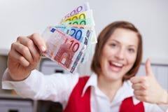 La donna con la giacenza monetaria sfoglia in su Immagini Stock