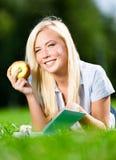 La donna con la mela legge il libro che si trova sull'erba verde Immagine Stock