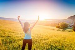 La donna con le armi si è alzata fino al cielo, celebrante il nuovo giorno fotografia stock libera da diritti