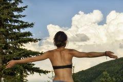 La donna con le armi stese gode dell'estate fotografia stock libera da diritti