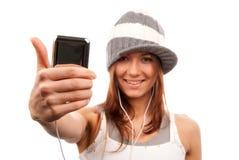 La donna con le cuffie del cellulare sfoglia in su Fotografia Stock Libera da Diritti
