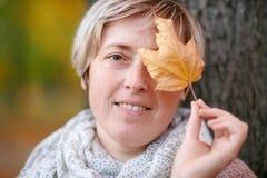 La donna con le foglie gialle è nel parco della città di autunno Alberi gialli luminosi fotografia stock