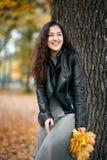 La donna con le foglie gialle sta vicino al grande albero nel parco della città di autunno fotografia stock libera da diritti