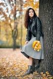 La donna con le foglie gialle sta vicino al grande albero nel parco della città di autunno fotografie stock