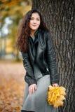 La donna con le foglie gialle sta vicino al grande albero nel parco della città di autunno immagini stock