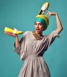 La donna con le scarpe blu e gialle sulla testa e sulle unghie manicure immagini stock libere da diritti