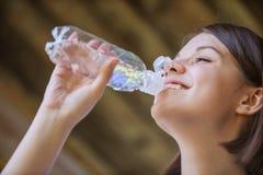 La donna con le spalle nude beve dalla bottiglia dell'acqua Fotografia Stock