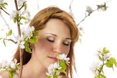 La donna con piacere che inala aroma di un fiore fotografie stock