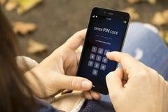 la donna con registra il telefono di codice del perno nel parco Fotografia Stock