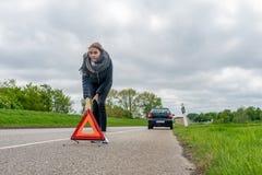 La donna con la ripartizione dell'automobile mette il triangolo d'avvertimento dietro l'automobile immagini stock libere da diritti