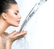 La donna con spruzza dell'acqua in sue mani Fotografie Stock Libere da Diritti