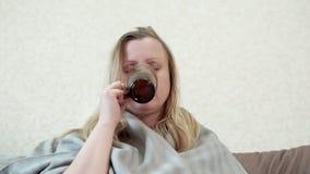 La donna con un freddo, influenza, beve il tè caldo con il limone È malata, febbre, brividi video d archivio
