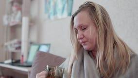 La donna con un freddo, influenza, beve il tè caldo con il limone È malata, febbre, brividi stock footage