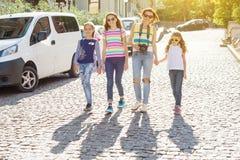 La donna con un gruppo di bambini sta ridendo, camminanti intorno alla città Fotografia Stock