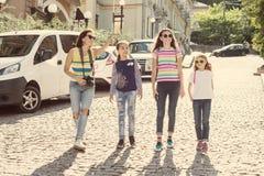 La donna con un gruppo di bambini sta ridendo, camminanti intorno alla città Immagini Stock
