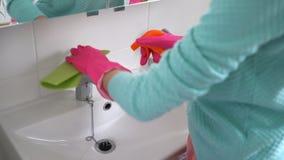 La donna con un guanto di gomma pulisce un lavandino nel bagno stock footage