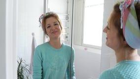 La donna con un guanto di gomma pulisce un lavandino nel bagno e sorride alla macchina fotografica video d archivio