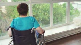 La donna con un'inabilità in una sedia a rotelle tira su alla finestra stock footage