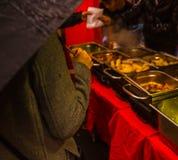 La donna con un ombrello in un acquisto grigio del soprabito ha imballato il pranzo Fotografia Stock