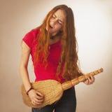 La donna con una scopa ha disegnato i chitarristi della roccia (foto umoristica) Immagine Stock