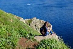 La donna con uno zaino si siede alla cima della roccia dal mare immagini stock libere da diritti