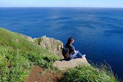 La donna con uno zaino si siede alla cima della roccia dal mare immagine stock libera da diritti