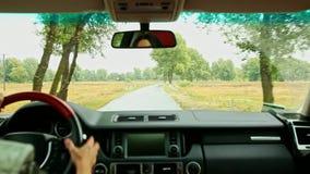 La donna conduce l'automobile straniera lungo la strada bagnata nella zona rurale in pioggia