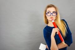 La donna confusa giudica la grande carta per appunti della matita disponibila Immagini Stock