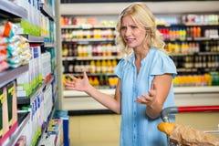 La donna confusa non conosce che cosa comprare Immagini Stock Libere da Diritti
