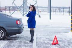 La donna congelata riscalda le sue mani sulla via ed aspettare un camion di rimorchio Fotografia Stock Libera da Diritti