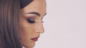 La donna considera la macchina fotografica su fondo beige lentamente archivi video